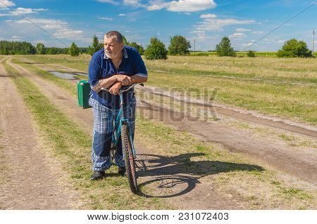 Senior With Green Suitcase Getting Ready To Ride On A Bicycle On A Country Road