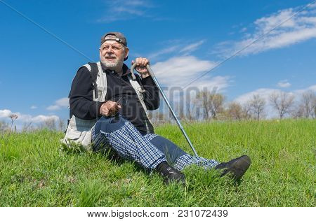 Elderly Hiker Sitting On Green Hill And Looking Into The Distance At Spring Season