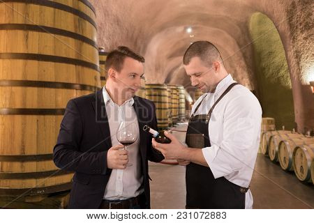 Portrait Two Men Tasting With Red Wine In A Vineyard. Professional Winemakers Standing In Front Of W