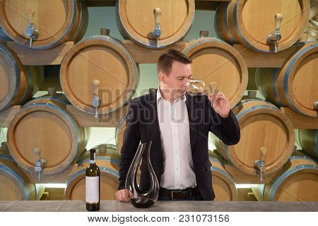 Young Handsome Man Sommelier Or Winemaker Tasting Red Wine In Wine Cellar