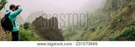 Traveler Holding Up The Camera To Take A Photo Of Amazing Steep Mountainous Terrain With Lush Canyon