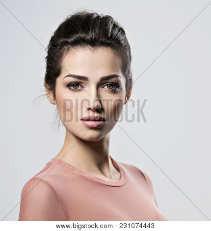 Portrait of an young beautiful  woman with  smoky eyes makeup. Pretty young adult girl posing at studio. Closeup attractive female face.