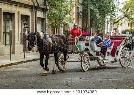 Savannah, Georgia - March 1, 2018: People Taking Part In A Guided Horse Carriage Tour In The City Of
