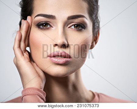 Portrait of an young beautiful  woman with  smoky eyes makeup. Pretty young adult girl posing at studio. Closeup attractive female face. Skin care concept
