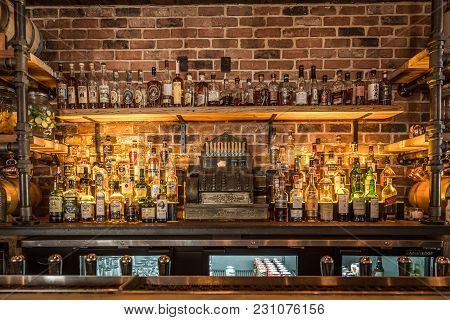 Savannah, Georgia - March 1, 2018: A View Of Liquor Bottles, Assorted Mixers, And A Vintage Cash Reg