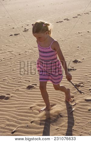 Little Girl In Colorful Dress Walking Alone On The Beach At Sunset With Light Behind. Spain.