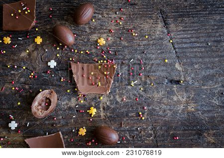 Easter Composition With Chocolate Eggs And Pieces Of Big Chocolate Egg On Old Rustic Wooden Backgrou