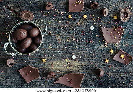 Easter Frame Background With Chocolate Eggs And Pieces Of Big Chocolate Egg On Old Rustic Wooden Tab