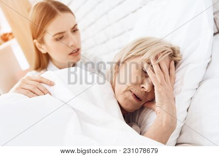 Girl Is Nursing Elderly Woman In Bed At Home. Woman Is Feeling Bad, Girl Is Concerned.