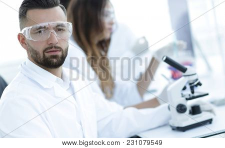 microbiologist and his colleagues are sitting in a modern laboratory
