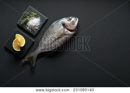 Delicious fresh gilt-head fish on dark vintage background. Healthy food diet or cooking concept poster
