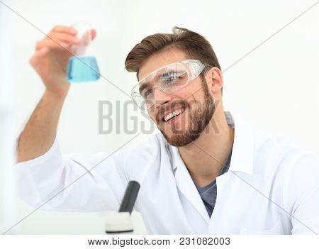 closeup. chemist holding a beaker with a solution