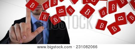 Mid section of mid adult businessman touching on invisible interface against bit coin symbol