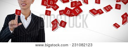 Businesswoman in suit touching invisible interface against bit coin symbol