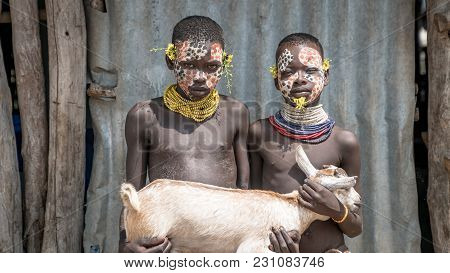 Omo Valley, Ethiopia, September 2017: Portrait Of Unidentified Karo Tribe Children Holding A Goat, C