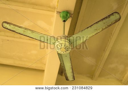Vintage Green Ceiling Fan On Ceiling. Old Ceiling Fan With Rust And Dust.