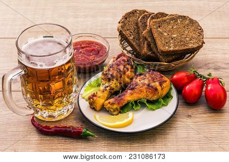 Grilled Chicken Legs Roasted On The Grill And Lettuce Leaves On Plate With Tomato Sauce In A Bowl, F
