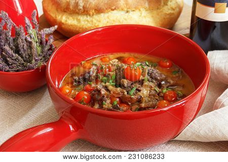 Duck Ragu With Cherry Tomatoes In A Red Pot On The Dining Table