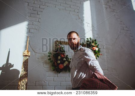 Handsome Man In Blank Taking Off His Red Jacket, White Bricks Wall Background