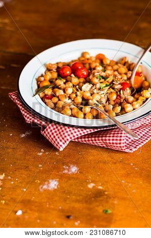 Chickpea Stew With Chicken, Capers And Cherry Tomatoes In A Plate On A Wooden Table, Selective Focus