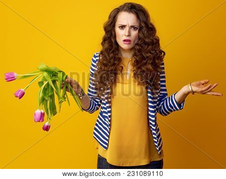 Woman On Yellow Background With Wilted Flowers