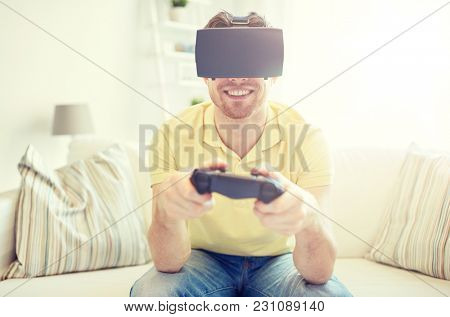 technology, gaming, entertainment and people concept - happy young man with virtual reality headset or 3d glasses playing video game with controller gamepad at home