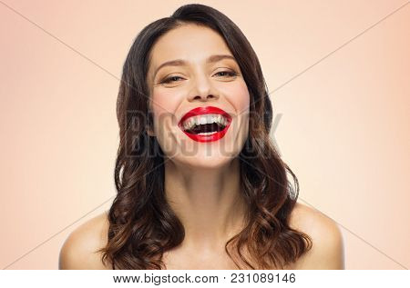 beauty, make up and people concept - happy laughing young woman with red lipstick over beige background