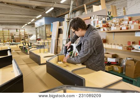 production, manufacture and industry concept - assembler working with electric screwdriver making furniture at workshop