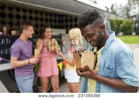 leisure, eating and people concept - happy african american man with wok and friends at food truck