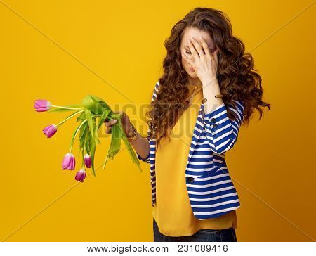 Stressed Woman Against Yellow Background With Wilted Flowers