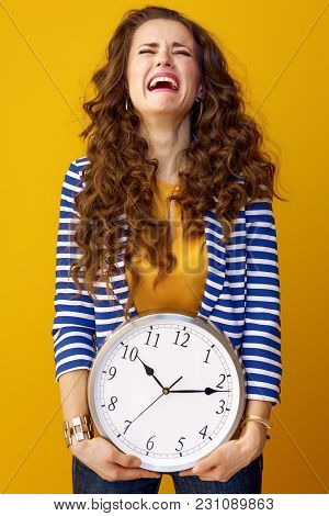 Sad Stylish Woman Isolated On Yellow Background With Clock