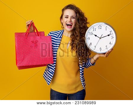 Woman On Yellow Background Showing Clock And Red Shopping Bags