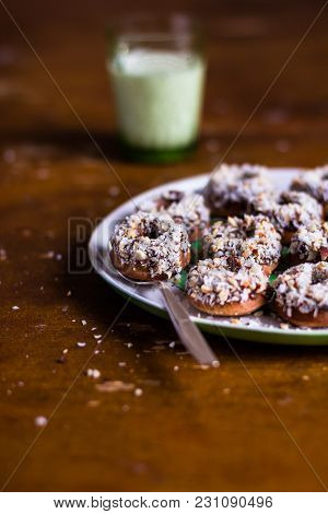 Heap Of Freshly Baked Homemade Donuts With Chocolate Cream And Coconut On A Plate On A Wooden Table,