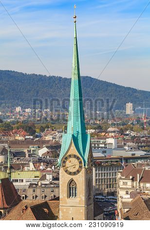Zurich, Switzerland - 24 September, 2014: view of the city of Zurich from the tower of the Grossmunster cathedral, clock tower of the Fraumunster cathedral in the foreground. Zurich is the largest city in Switzerland.