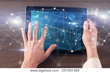 Hand using tablet with linking graphs charts  report and informational flow concept