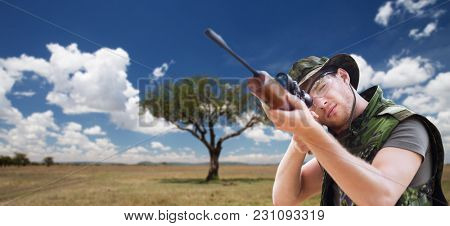 hunting, army, military service and people concept - young soldier, ranger or hunter with gun aiming or shooting over savannah background