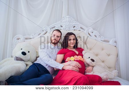 Young Family Prepares To Become Parents. Husband Gently Hugs His Pregnant Wife Female At Home On The