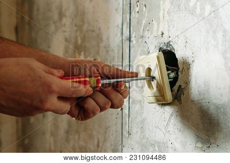 Close-up Of Person's Hand Installing Socket On Wall At Home
