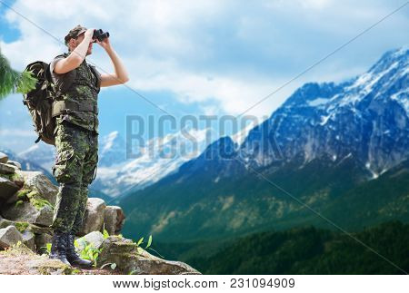 hunting, army, military service and people concept - young soldier with backpack looking to binocular over mountains observing area