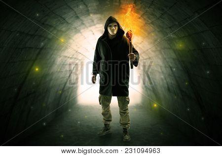 man with burning flambeau walking in a dark tunnel