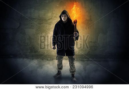 Wayfarer with burning torch in his hand in front of a crumbly wall concept