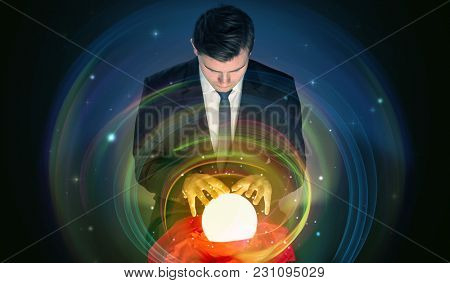 Young handsome man looking to the future of the universe in a crystal ball