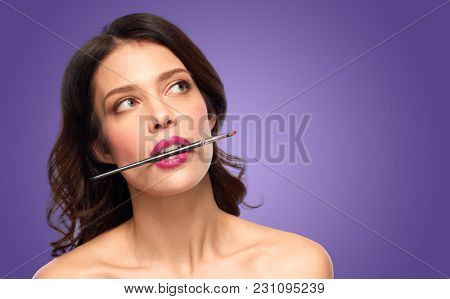 beauty, cosmetics and people concept - beautiful woman with berry lipstick holding make up brush by teeth over ultra violet background