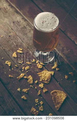 Glass Of Cold Pale Beer With Some Tortilla Chips On A Rustic Wooden Table. Selective Focus On The Fo