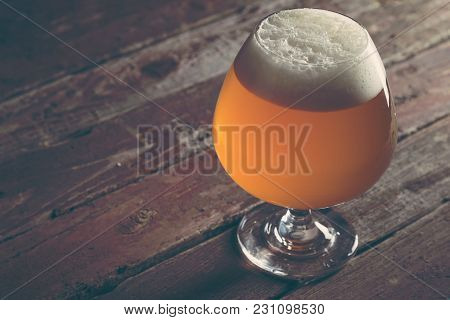 Glass Of Cold Pale Unfiltered Beer On A Rustic Wooden Pub Table