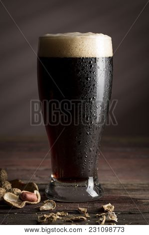 Glass Of Cold Dark Beer With Foam Placed On A Rustic Wooden Table With Some Peanuts Next To It. Sele