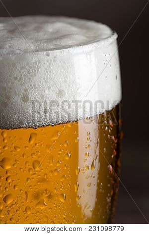Detail Of A Wet Glass Of Cold Light Beer With Foam. Selective Focus