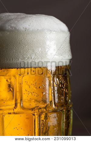 Detail Of A Wet Jug Of Cold Light Beer With Foam. Selective Focus