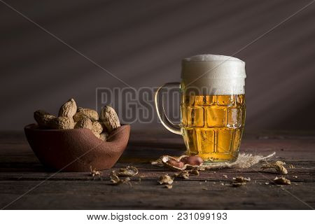 Mug Of Light Beer With Foam Placed On A Burlap Coaster And A Bowl Of Peanuts On A Rustic Wooden Tabl