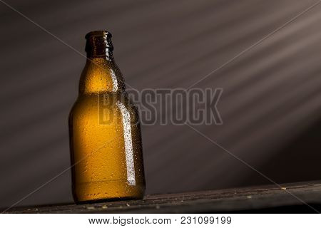 Well-chilled Wet Beer Bottle Placed On A Rustic Wooden Table In A Bar